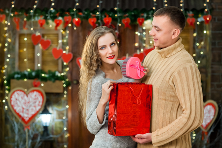 couple in love celebrate valentines day. Man making surprise on holiday and present rose box to his girl. Girl enjoy present. Concept of happy valentines day