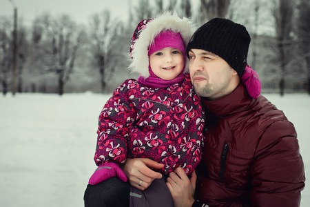 happy young father in claret coat with little daughter in pink pattern coat smiling, hugging and spending time outdoors in the winter park. Concept of happy family