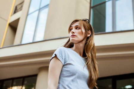 redhead hipster girl in a gray shirt walking in the street. Concept of modern freedom hipster human, close up portrait Stock fotó
