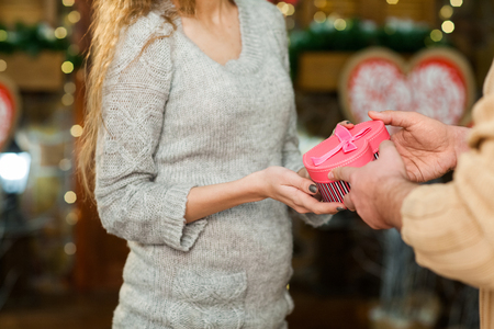 Couple in love celebrate valentines day. Man giving present in pink box to his pretty woman Stock Photo