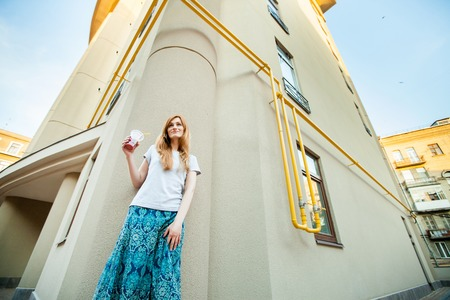 attractive redhead girl with cocktail posing near building in the street. slim woman in a gray shirt and a blue long skirt walking around city. Concept of modern freedom hipster human Stock Photo