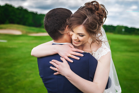 Beautiful bride and handsome groom celebrating wedding day. Young newlyweds smiling and hugging in green nature. Concept of happy moment Stock Photo