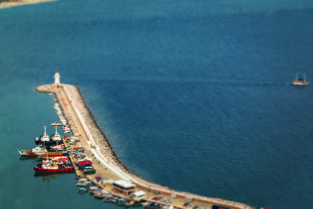 large pier with lighthouse situated on it, surrounded by ships and boats .view from a top. free space for text Stock Photo