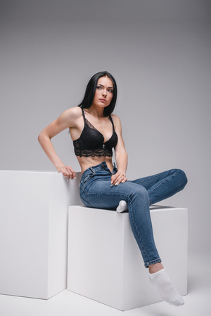 attractive girl in black brassiere and jeans sitting on cube in photostudio