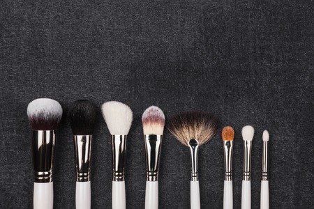 row of brushes in white covering different in shapes and in use. tools laying on the black background. Stock Photo