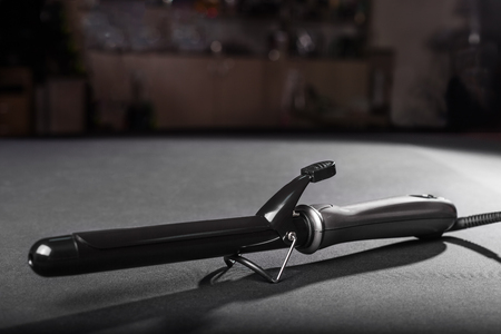 trendy black curling iron laying on a grey table in a salon.