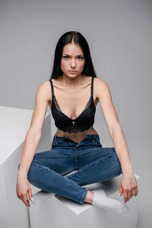 attractive sexy woman in black brassiere and jeans sitting in lotus pose on cube in studio on gray background