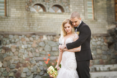 handsome groom hugging his pretty bride holding bouquet softly on the background of old stone historical building Archivio Fotografico