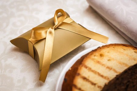 Wedding bonbonniere in beautiful gold packing with bow and hot toast on the festive table Archivio Fotografico