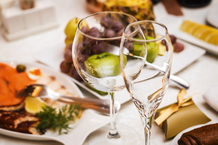 Two fancy wedding goblets glasses laying on the table with foods at the wedding banquet Reklamní fotografie