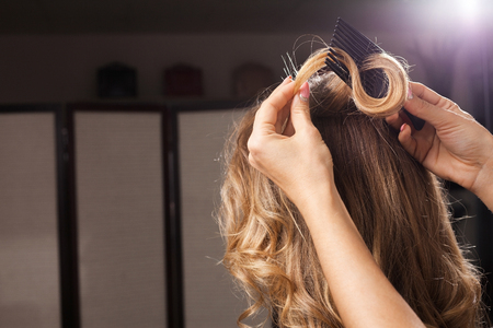 hairdresser combing a perfect hair curl of a model carefully holding its tip in a beauty studio. concept of making hairdos Foto de archivo - 103540601