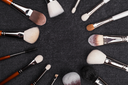 make up brushes different in shapes and in use. tools laying hair to hair making a circle themself on the black background. free space for text