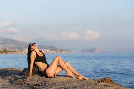 Elegant sexy model in the black bikini on the sun-tanned slim and shapely body posing near an ocean. Sunny day, vacation holiday, resort and summer time