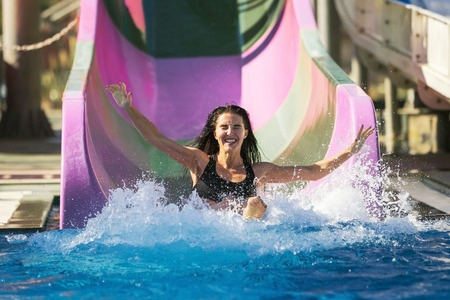 pretty brunette slim woman with spreading hands on the rubber ring having fun coming down on the purple water slide in the aqua park. Summer Vacation. Weekend on resort