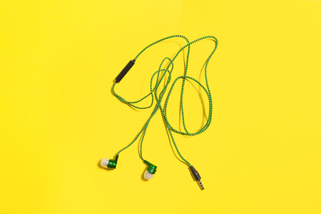 new bright green vacuum earphones lying negligently on a yellow background. top view. free space for advertising text