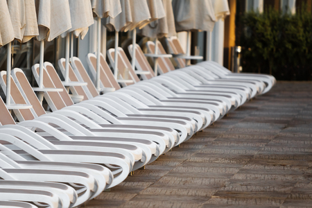Row of white plastic deck chairs with umbrellas near the swimming pool. holidays concept Фото со стока