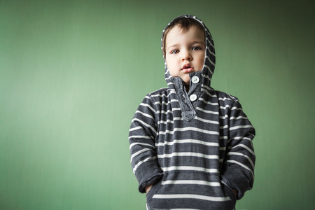 upset cute young boy holding hands in pullover pockets.Free space for advertisement Stock Photo