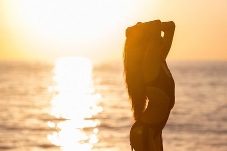pretty young woman with long dark hair tanning in black swimwear against an ocean and sunset . concept of happy holiday and resort time. silhouette over sunrise Stock Photo