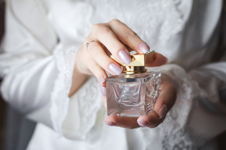 Close up shoot of a luxury perfume flacon being holded in manicured hands of elegant bride wearing white dressing gown