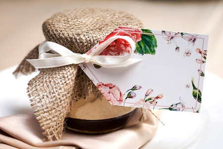 gift jam decorated with a ribbon and a sackcloth as a present for guests standing at a wedding party table. concept of bridal presents