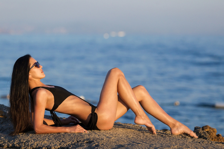 beautiful woman in the black bikini on the tanned slim and shapely perfect body and fashion sunglasses posing near an ocean. Sunny day, vacation holiday, resort and summer time Stock Photo