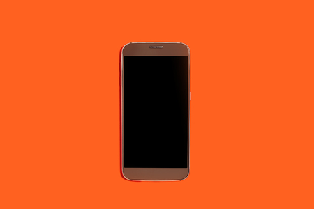 new modern smart phone lying on an orange background with a turned off screen. concept of gadgets