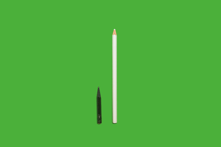Black small used and white long new pencils lying on a green background. concept of office and educational chancery