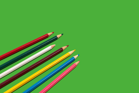 colored pencils lying diagonally on a green background. concept of office and educational chancery. free space for advertising text
