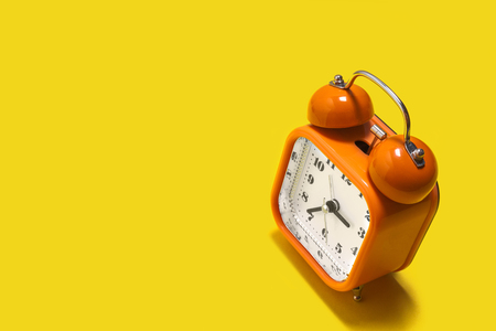 Vintage style orange metal alarm clock with bells standing on the yellow background isolated. back to school concept. free space for advertising text