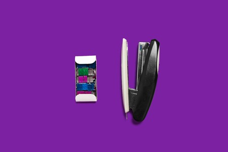 metal black stapler with box of braces lying on a purple background . concept of office chancery. free space for text Фото со стока