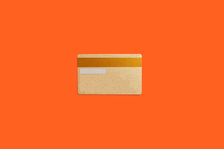 vip gold credit card lying isolated on an orange background. concept of money saving. free space for text