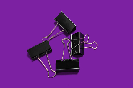 paper clips for office stationery lying on the purple surface. concept of business or educational equipment 免版税图像