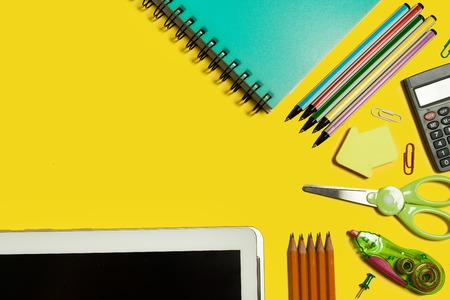 various school and office stationary and gadgets lying on a yellow background. free space for text