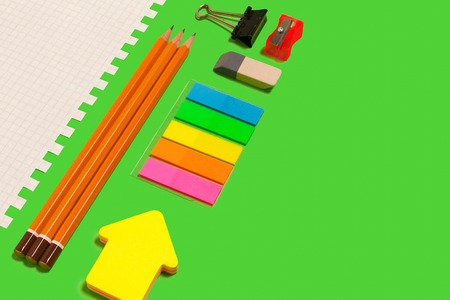 white sheet of paper, pencils, stickers, sharpener, eraser and a clinch lying diagonally on a green surface. concept of educational chancery. free space for advertising text
