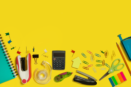 multiple school and office suplies and gadget lying on a yellow background Stock Photo