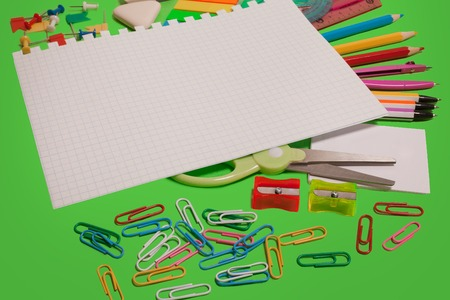 colored pencils and pens, clips, scissors, sheet of paper and a ruler lying on a green background. concept of office and educational chancery. free space for text Stock Photo