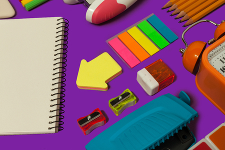 colored various school stationary lying on a purple surface. concept of office and educational supplies 写真素材