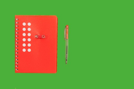 red new beautiful spiral notebook lying near a pen on a green background. concept of office stationary
