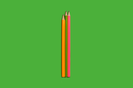 two new pencils lying on a green background. concept of office supplies. free copyspace
