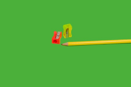 two sharpeners lying near a pencil on a green background. concept of office and school supplies