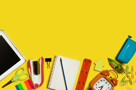 multiple school suplies and gadgets lying on a yellow surface. free space for advertising text