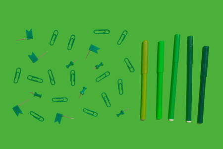 bright plastic felt pens, paper clips and pushpins lying on a green surface. concept of office supplies