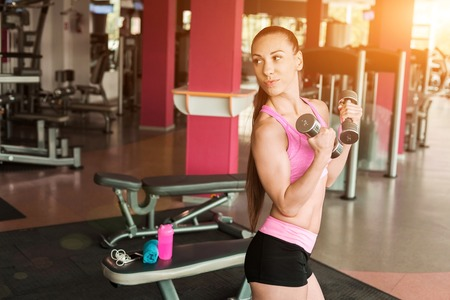 Athletic beautiful girl wearing pink and black sportswear doing exercise using dumbbells in an equipped gym. Strength and motivation concept 版權商用圖片