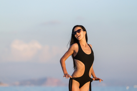 beauty woman in the black bikini on the tanned slim and shapely perfect body and fashion sunglasses posing near a sea. Sunny day, vacation holiday, resort and summer time