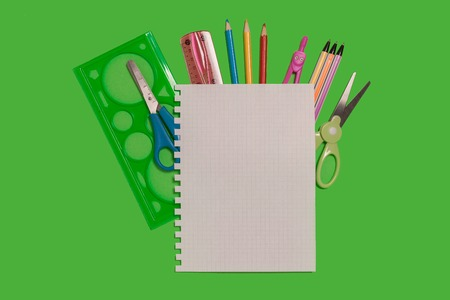 colored pencils and pens, scissors, sheet of paper and a ruler lying on a green background. concept of office and educational chancery. free space for advertising text