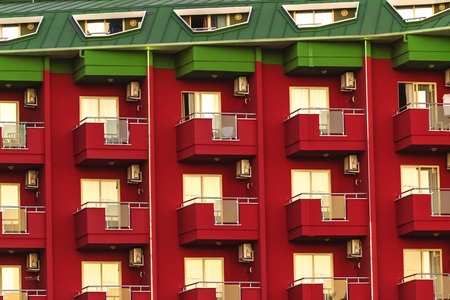 modern contemporary bright red building. hotel with lots of balconies and windows and green roof