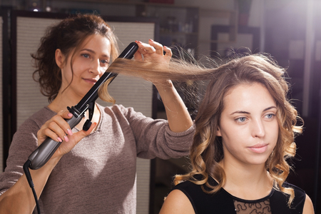 hairdresser making a hairdo with curls to a beautiful model in a beauty salon at a master class. concept of professional stylists studying