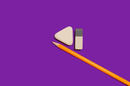 new pencil and two different in shape erasers lying on a purple background. concept of office supplies. free space for text