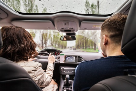 Beautiful couple sitting on the front passenger in vehicle. woman is driving a car. view from a back of young pair. travel and adventure concept