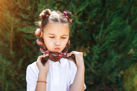 lovely child girl wearing white shirt having fun holding her pigtails in a sunny summer park. pine trees on a background